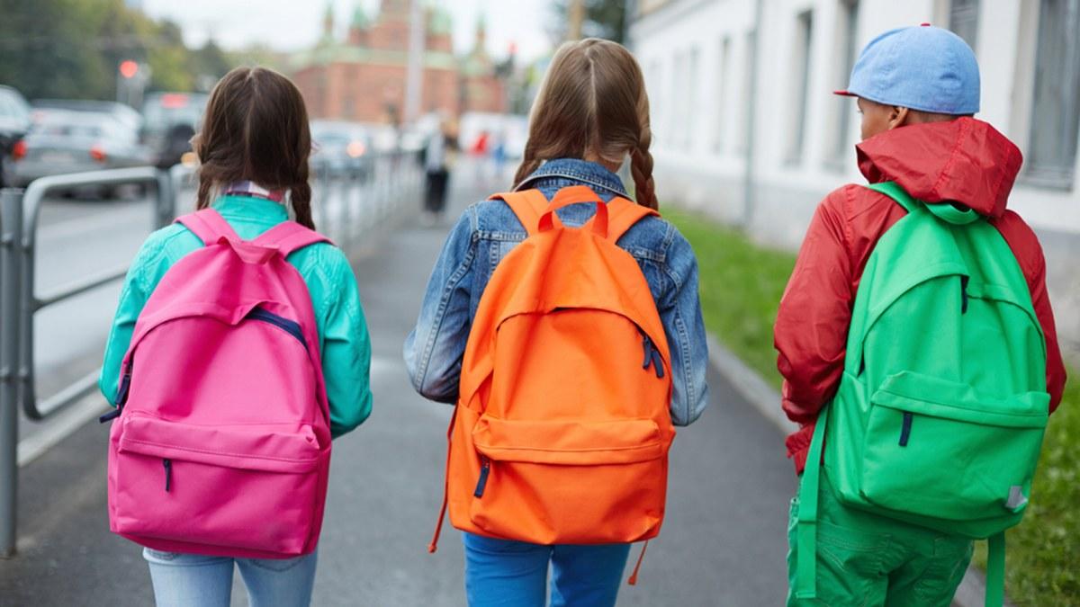 niños con mochilas escolares